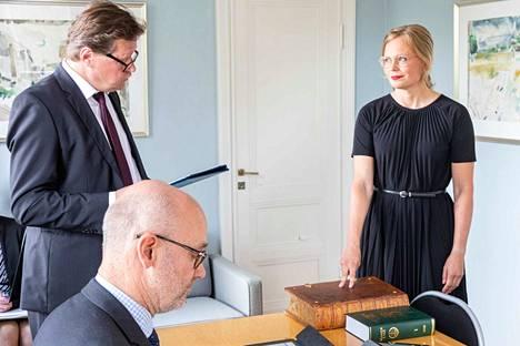 Hanna Kosonen (kesk.) vannoi ministerinvalansa sormet raamatulla ja tuomarinvakuutuksen sormet lakikirjalla.