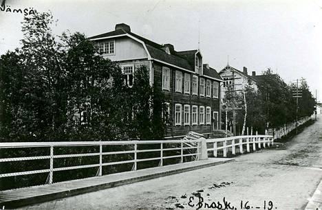 Seppolan sillan aluetta 1919. Vasemmalla nykyisin liiketalo, jossa muun muassa valaisinmyymälä ja sen yläpuolella entinen Nordea.  Kuvan vasemmanpuoleisessa talossa toimi Jämsän posti ja puhelinkeskus vuodesta 1915. Tampereen Osake-Pankki oli talossa 1920-luvulla. Vuonna 1937 sen osti Jämsän Osuuskassa. Taloa muistellaan yhä posti- tai kassatalona. Kuvaaja Emil Brask.