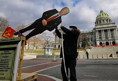 Donald Trumpia vastaan mieltään osoittaneet toivat pahvijäljennöksen keskiviikkona kautensa päättävästä presidentistä Pennsylvanian osavaltion hallintorakennuksen eteen viikonloppuna.