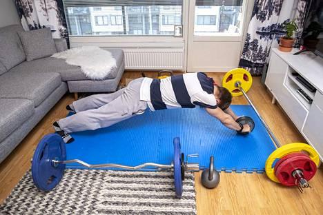 Luukas Saha treenaa keskivartalon lihaksia voimapyörällä.