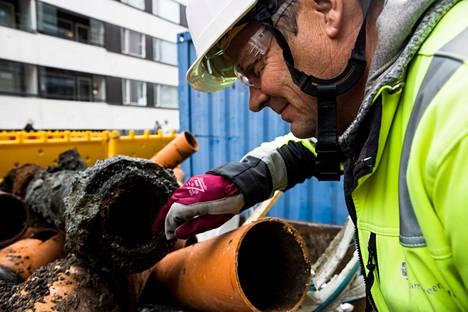 Näsilinnankadulla Tampereella on tehty viemäritöitä ja erotettu jätevesi- ja sadevesiviemärit toisistaan. Vastaava työnjohtaja Jukka Hepokari Tampereen Infra oy:stä näyttää, kuinka musta ja epätasainen on 121-vuotias vesiputki.
