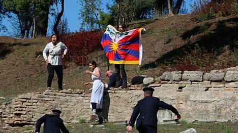 Pekingin olympialaisten tulen sytytystilaisuudessa Kreikassa mielenosoittaja pitää käsissään Tiibetin lippua.