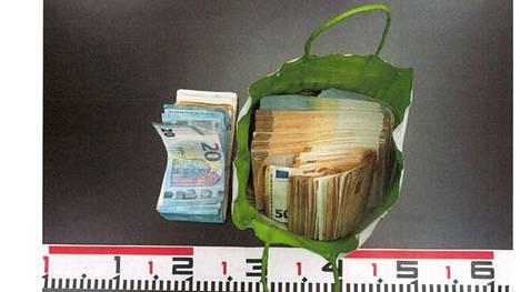 Poliisi löysi esitutkinnassa suuria määriä käteistä rahaa. Kuvan vihreässä paperikassissa on lähes 50 000 euroa käteistä.