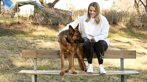 Nina Lindstedt koiransa Topi the Dogin kanssa puistonpenkillä.