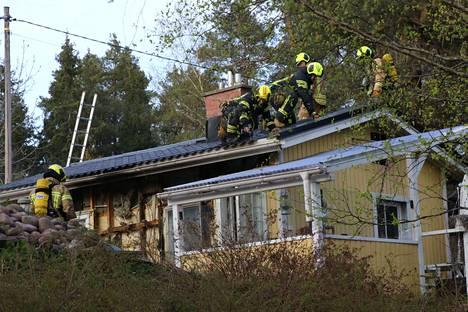Palokunta purki palossa vaurioituneen puutalon kattorakenteita.