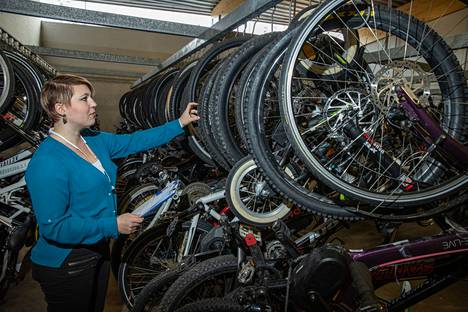 Pyörät on nosteltu varastossa tankoihin siinä järjestyksessä, kun ne ovat poliisille tulleet. Laura Kinnusen edessä olevassa tangossa on 53 takavarikoitua pyörää, jotka myydään torstaina.