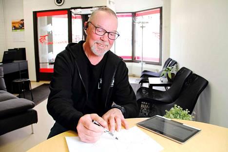 Ari Niittumaa piirtämässä toimittajan toiveesta esimerkkiä Jämintien ja Keskuskadun risteyksessä ajamisesta uuden tieliikennelain mukaisesti. Uusi laki tuo monia uudistuksia, mutta käytännössä autoilu muuttuu varsin vähän.