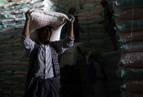 Jemeniläinen työntekijä purki huhtikuun alussa YK:n ruokaohjelman avustuskuljetusta maan pääkaupungissa Sanaassa. Ruokaohjelman suoran avun varassa on ympäri maailmaa noin sata miljoonaa ihmistä.