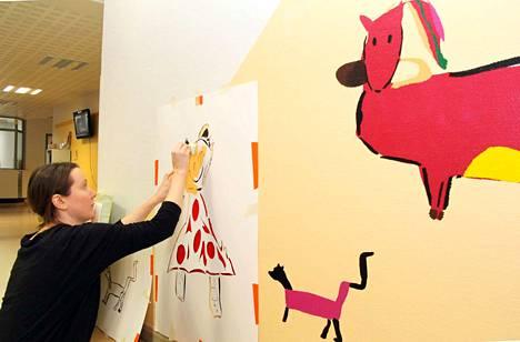 Pinkki poni paranee -seinämaalauksen hahmot ovat lasten piirustuksista suurennettuja. Leikkinurkkauksen vasemmanpuoleisella seinällä hahmot ovat jo hyvän hoidon ansiosta parantuneet. Kuvataitelija Heidi Hänninen työskentelee.