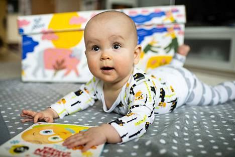 Äitiyspakkauksessa oleva ensikirja on monen vauvan mieleen. Kuvassa myös pakkauksen viltti ja laatikko.