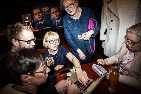 Kokoomuslainen Leena Kostiainen (keskellä) oli toista kertaa ehdolla ja jännitti tuloksia. Hän oli menossa eduskuntaan ennakkoäänten perusteella, mutta menetti paikkansa, kun ääntenlaskenta eteni. Kostiaisen seurana muun muassa Anneli Taina, ex-ministeri (seisomassa).