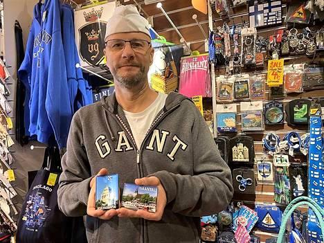 Postikorttiaika on ohi, ja nykyään turistit haluavat seinämagneetteja paikallisista aiheista, näyttää Henri Nevari kaupassaan.