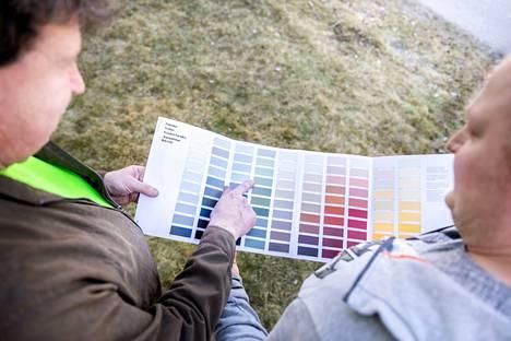 Jani Koivunen (oik.) auttaa Ari Haasiosaloa valitsemaan taloonsa oikean maalin ja siihen saman sävyn kuin talon nykyisessä pinnassa on.