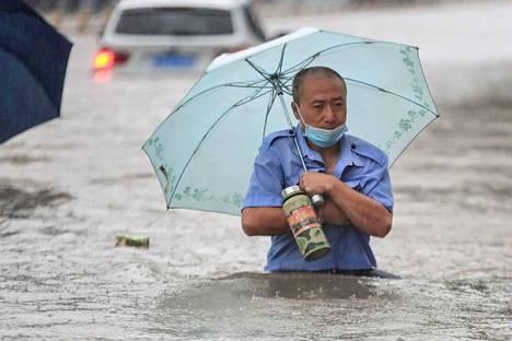 Mies kävelee tulvaveden täyttämää katua pitkin. Kuva on otettu 20. heinäkuuta 2021 Zhengzhoussa Henan provinssissa.