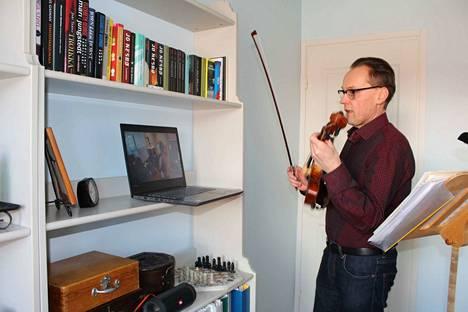 Viulusoiton opettaja Aarne Miettinen käyttää etäopetuksessa apuna läppäriä. Oikean soittoasennon opastaminen on etänä vaikeaa.