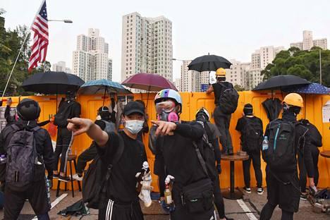 Mielenosoittajat seisoivat rakentamiensa barrikadien edessä Hongkongin baptistiyliopiston ulkopuolella keskiviikkona. Monet yliopistot ovat muuttuneet taistelutantereiksi.