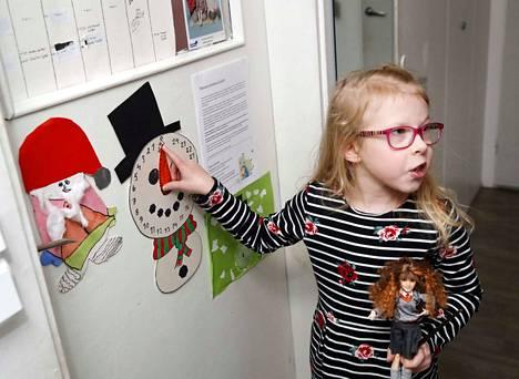 Eveliina Saarinen näyttää, miten perheessä pidetään lumiukkomittarin avulla selkoa ensin siitä, montako päivää on joulukuun alkuun, sitten jouluun.