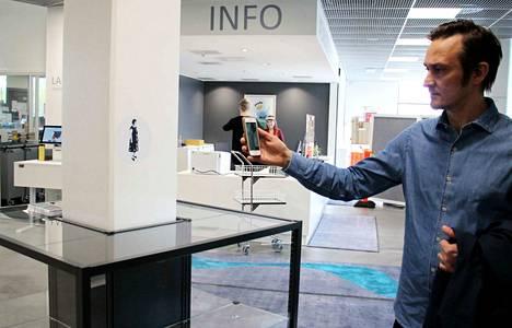 Jarno Vesala esittelee Katkelmia-teoksen osaa, jossa valokuvia ja videoprojisoinnin piirroshahmoja löytyy kirjaston eri osastoilta lisätyn todellisuuden AR-sovellukseen piilotettuna.