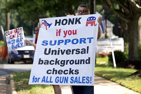 """Aseuudistuksen kannattajat protestoivat ase-etujärjestö NRA:n pääkonttorin edustalla Virginian Fairfaxissa elokuun puolivälissä. """"Tööttää jos kannatat taustatarkistuksia kaikille aseenostajille"""", lukee kyltissä."""