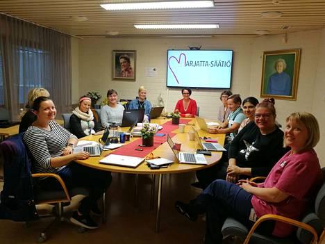 Marjatta-Säätiön vastuuhenkilöt istahtivat tiistai-iltapäivän päätteeksi kokoukseen Vantaalla. Toiminnanjohtaja Mari Niemi-Saari logon alla.