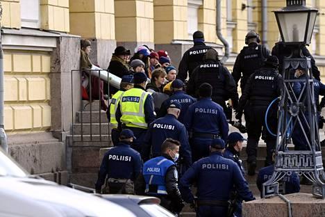 Poliisi siirtää mielenosoittajia pois paikalta.