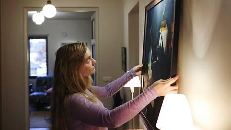 Anna Niskanen asettelee Amanda Coten maalausta seinälle. Kysyimme asiantuntijoilta, mitä taulujen ripustuksesta kuuluu tietää.