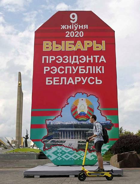 """Nuori mies ajaa potkulaudallaan Minskissä ohi jättiläiskyltin, jossa lukee: """"9. elokuuta 2020 Valko-Venäjän presidentinvaalit"""". Etenkin nuoret toivovat maansa eurooppalaistumista."""