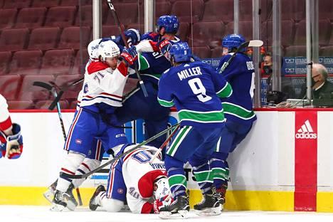 Vancouverin Tyler Myers (takana, numero 57) sai Montreal-pelaajat kimppuunsa hänen taklattuaan Joel Armiaa ulosajon vastaisesti.