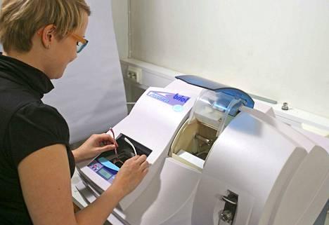 Optikko Piila toimittaa linssit nopeasti, sillä oma hiomo palvelee silmälasiasiakkaita. Optometristi Anna Linninen valmistelee silmälasilinssien hiontaa.