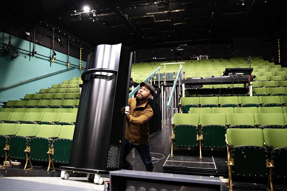 Näyttelijä Juho Milonoff työryhmineen testaa, voisiko teatteriesitysten turvallisuutta parantaa mikrobeja tuhoavan ilmanpuhdistuslaitteen avulla. Kuva Kom-teatterin salista.