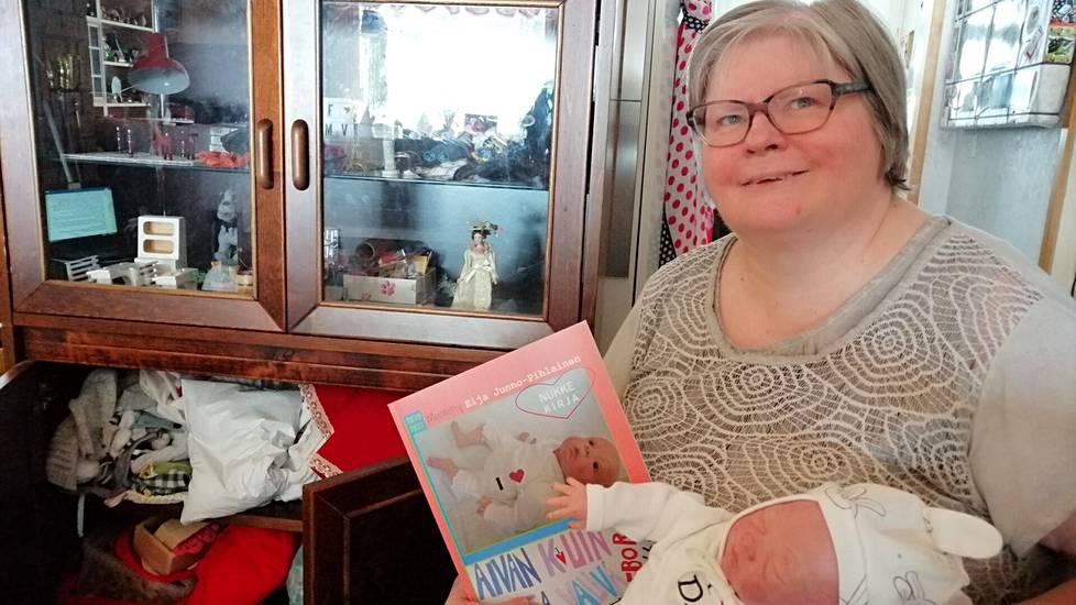 Eija Junno-Pihlainen on harrastanut reborn-vauvanukkeja muutaman kuukauden ja kokosi nukkemaailmastaan värikuvajulkaisun huhtikuussa 2021. Taustalla kaapissa on käsistään kätevän nukkemummyn tekemiä vauvanvaatteita.