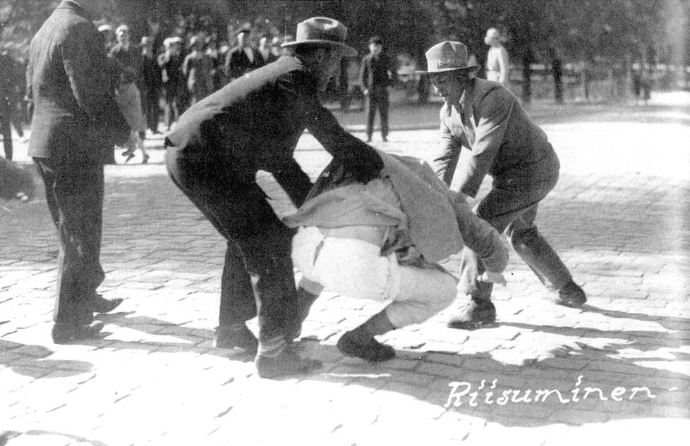 """Lapuanliikkeen miehet pahoinpitelivät Eino Niemisen ja riistivät vaatteita hänen yltään Vaasassa 4. kesäkuuta 1930. Saadakseen parempia kuvia, valokuvaaja Paavo Poutiaisen kerrotaan yllyttäneen tekijöitä. Kuuluisa otos sai nimen """"Riisuminen""""."""