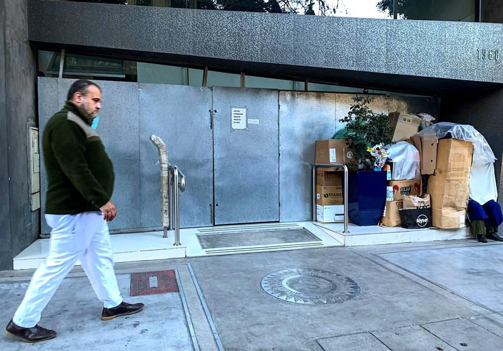 Koditon henkilö istuu suljetun liiketilan edessä Argentiinan Buenos Airesissa. Talousongelmissa pitkään ollut maa ajautui maksukyvyttömyyteen koronapandemian aikana.