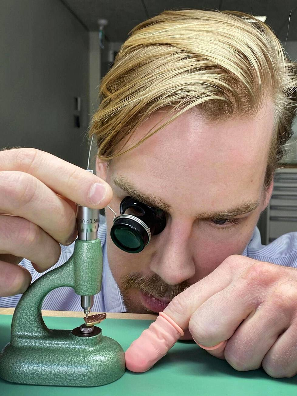 Kelloseppä Eric Wikholm tarkastaa Omega Seamasterin rattaiden akseleiden pintojen kunnon ennen kellon laittamista myyntiin.
